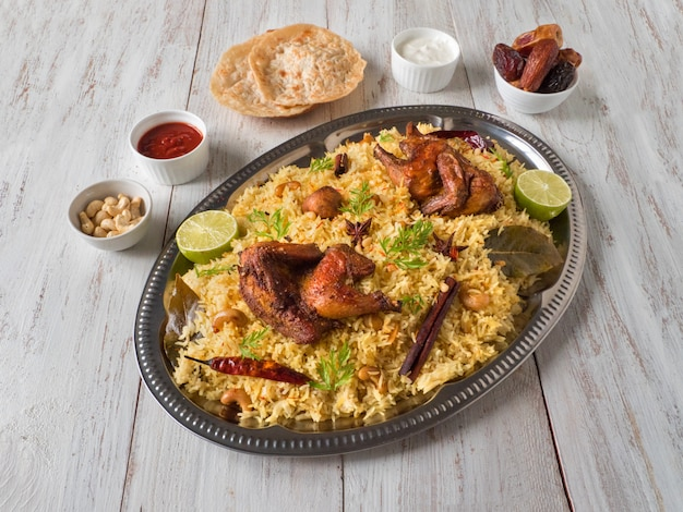 木製のテーブルの日付とチキンマンディ。アラビア料理。