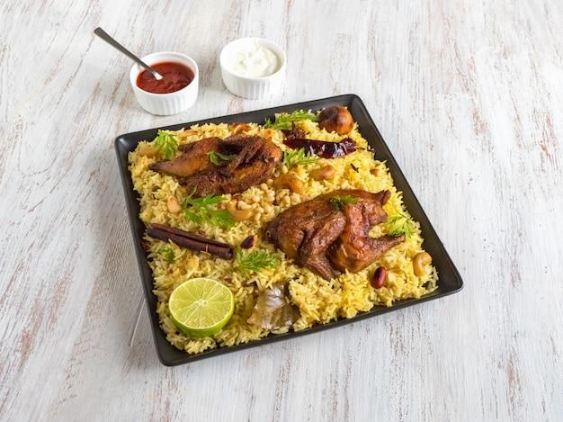 自家製チキンビリヤニ。アラビアの伝統的な食べ物は肉とカブサをボウルします。上面図