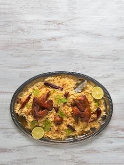 自家製チキンビリヤニ。アラビアの伝統的な食べ物は肉とカブサをボウルします。