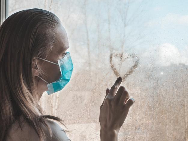 悲しいことに窓辺に立っている医療用使い捨てマスクを着た女性が濡れたコップにハートを描く