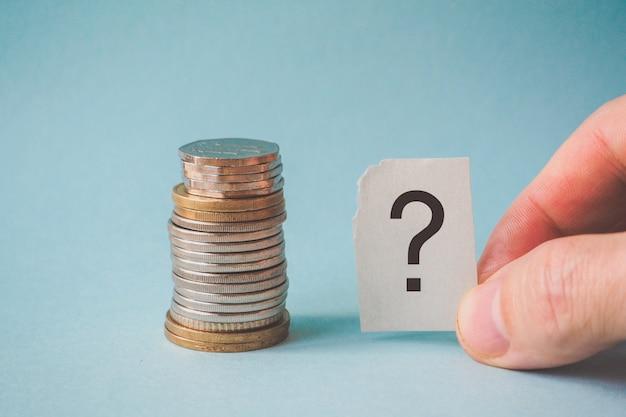 Знак вопроса и стопка монет.