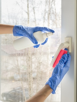 コロナウイルス消毒。窓を消毒する人々。ゴム手袋の医師が窓のハンドルを消毒剤とスポンジで消毒