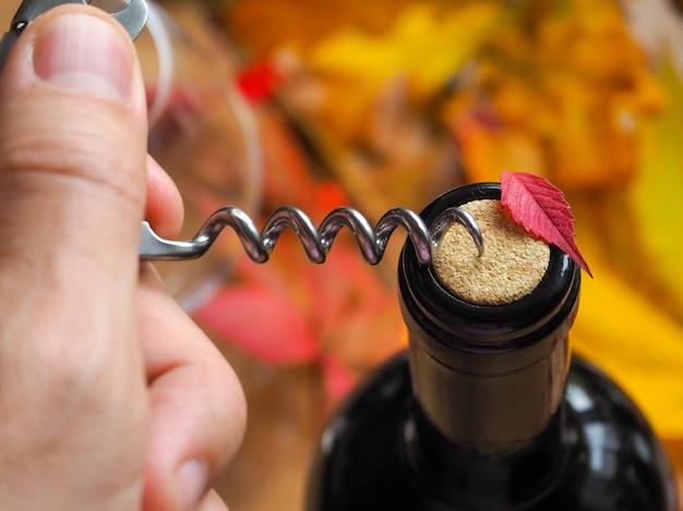 コルク栓抜きと赤ワインのボトル。ワインのボトルを開けます。閉じる。