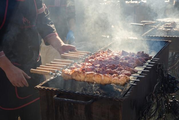グリルで肉を調理します。グリルからの煙、戸外でのバーベキュー。お祝いのバーベキュー。
