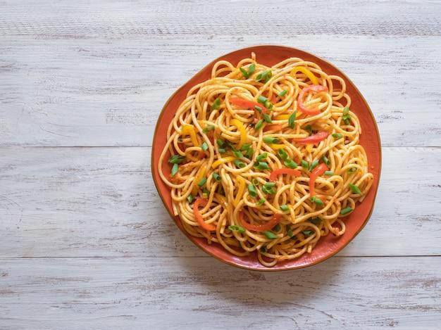 客家麺はインドシナの人気レシピです。皿に野菜とシェズワン麺。上面図。