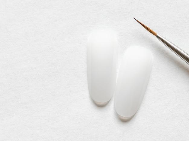 Концепция творческого маникюра. чистые кончики ногтей и кисточка для маникюра на белой стене