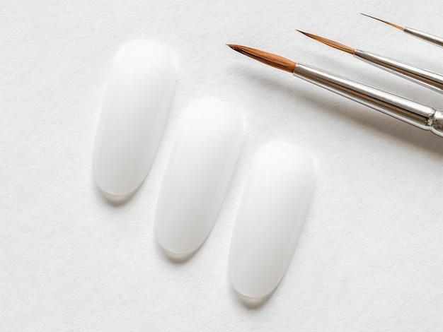 Концепция творческого маникюра. чистые наконечники и кисти разных размеров для маникюра на белой стене