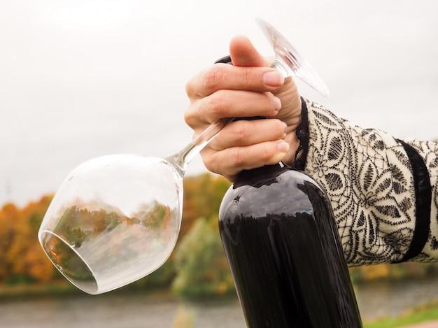 女性の手で赤ワインのボトル
