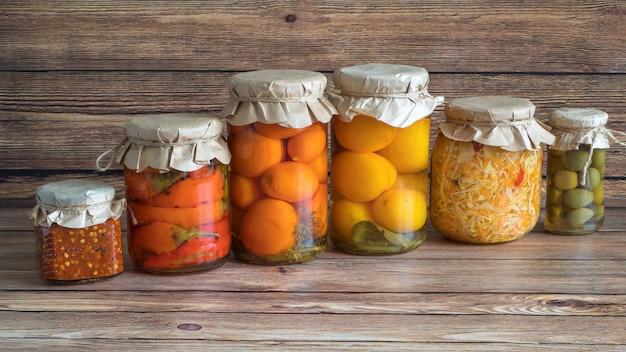 Маринованные соленья разнообразные консервирующие банки на кухонном деревянном столе. ферментированная домашняя еда