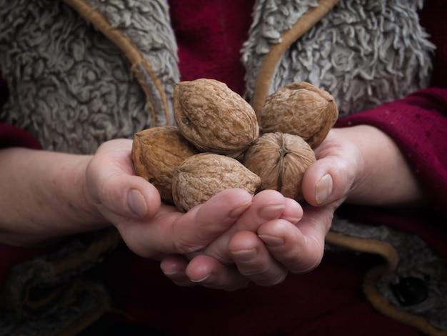 Человек держит в руках грецкие орехи.
