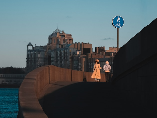 橋を渡って後ろから歩くカップル