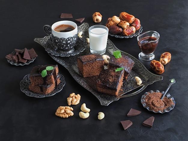 日付、ブラウニー、ミルク、コーヒーが黒い表面に配置されています。お祝いラマダンの背景