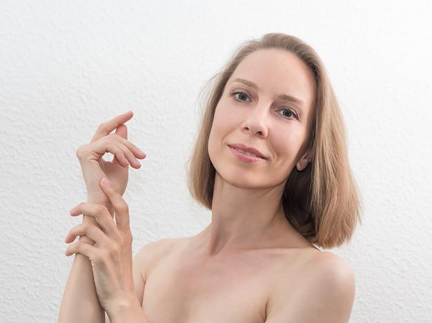 白い壁に彼女の顔に触れる美しい中年の女性の肖像画