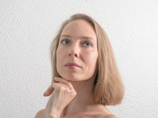 Портрет красивой женщины среднего возраста, касаясь ее лицо на белой стене