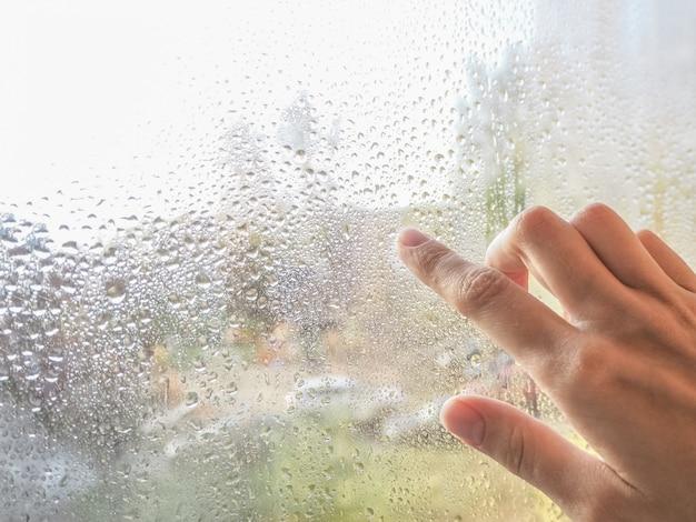 Палец у мокрого окна