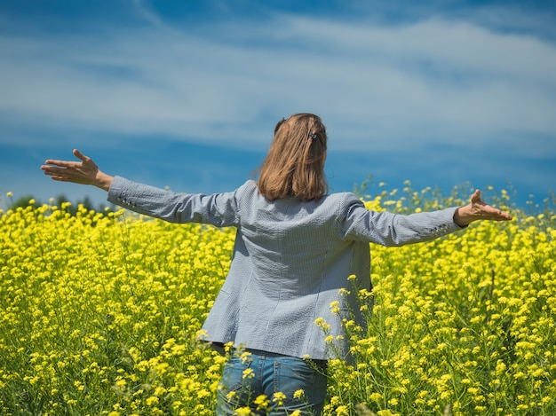 Счастливая девушка, наслаждаясь красотой солнечного летнего дня в поле желтых цветов