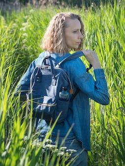 Вид со спины блондинки в джинсовом платье снимает рюкзак на дорожке в высокой траве