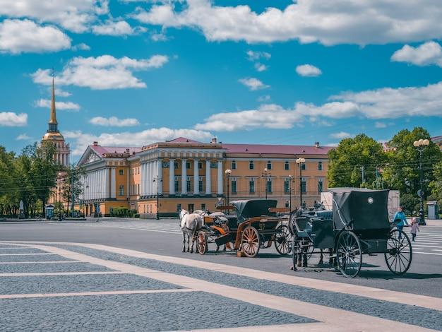 Вид зимнего дворца с каретой и лошадьми в санкт-петербурге. россия