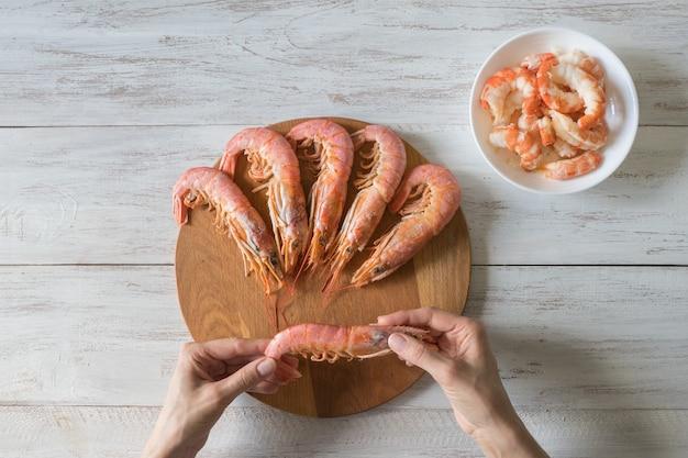 エビの手による皮むき。調理した新鮮な巨大なエビをクローズアップ