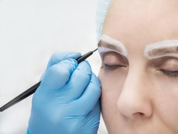 アイブロウシャドウ適用、眉モデリングメイク、目のクローズアップ。女性の顔の眉毛の入れ墨をしている美容師。美容手順。