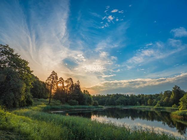 湖のほとりに美しい夏の夕日。