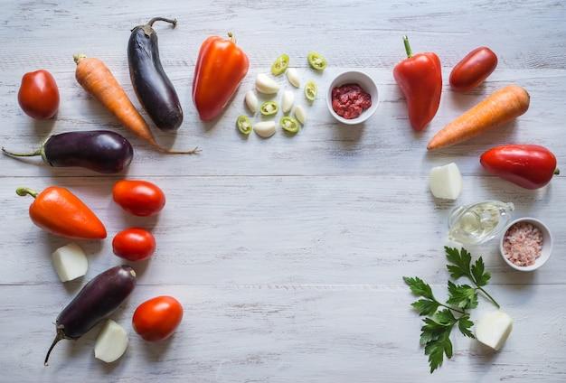Овощи разложены на белом деревянном столе. продовольственный фон.