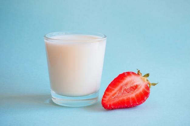 牛乳と青色の背景に熟したイチゴのガラス