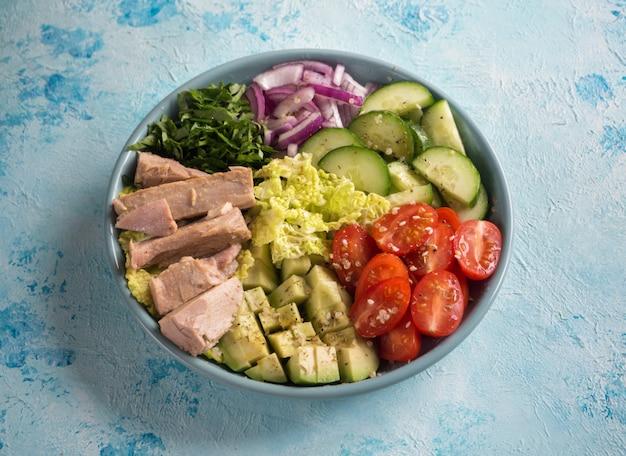 Салат из авокадо и тунца на синем столе. вид сверху.