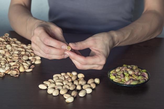 Руки чистят фисташки орехами. концепция ручного труда.