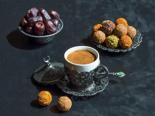 日付と黒いテーブルの上のカルダモンとトルココーヒー。