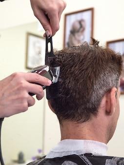 男性用散髪機。バリカンの助けを借りて男性の髪。