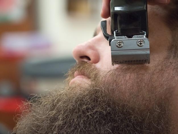 理髪店でバリカンでひげをトリミングします。閉じる。