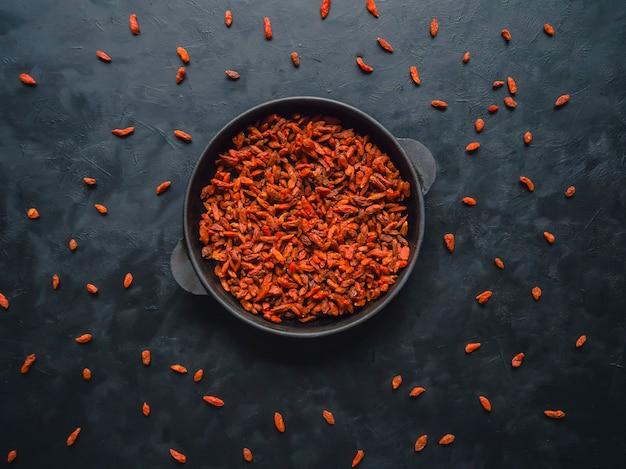 Ягоды годжи на черном столе. суперпродукты для здорового питания. вид сверху.