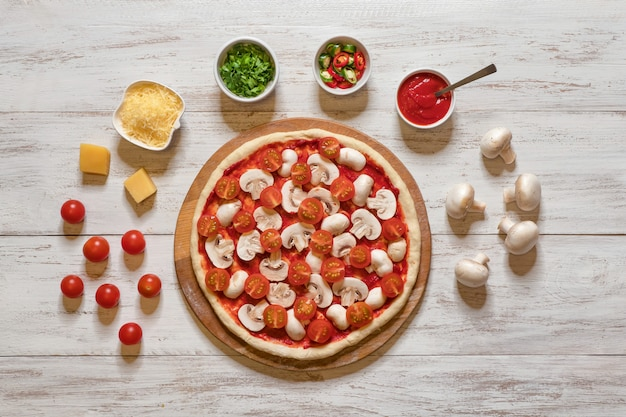 トマトとキノコの生ピザ。フラットピザの材料は、木製のテーブルに横たわっていた。