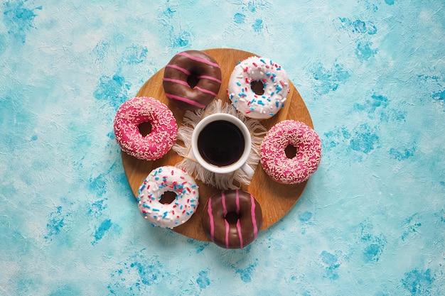 青いテーブルに色とりどりのドーナツのお菓子。青い石のカラフルなドーナツ。