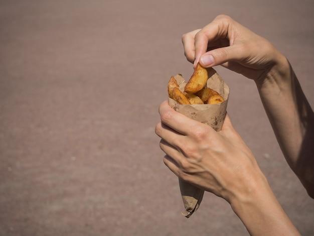 Картофельные закуски в руках. закуска на ходу. вкусные картофельные чипсы.