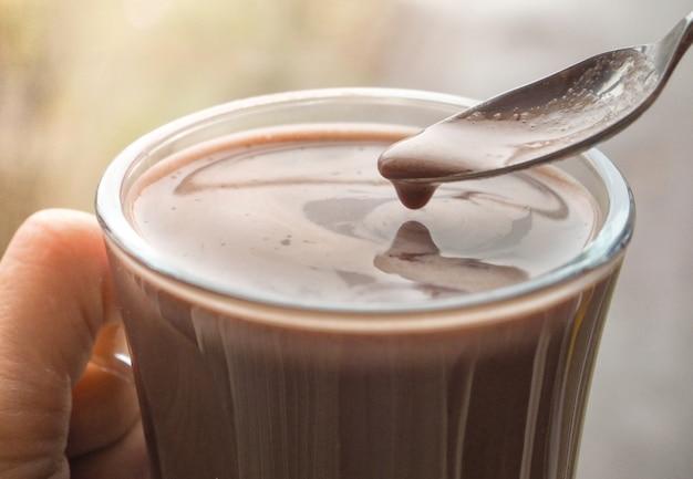 Пенный черный кофе на чайной ложке. чашка кофе.