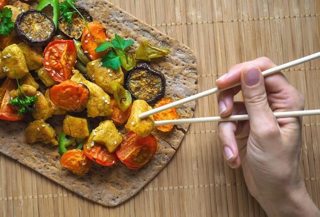 Рука держит палочки для еды кусок курицы. запеченные овощи на гриле с кусочками куриного карри