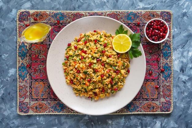Рамадан еда. салат с кус-кусом и гранатом.