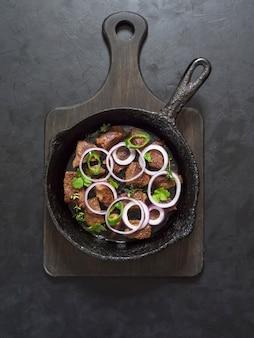 古い鍋で肉をローストします。黒いテーブルで揚げ肉とパンします。上面図。