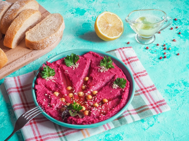 青いテーブルの上の皿に伝統的な赤いフムス。