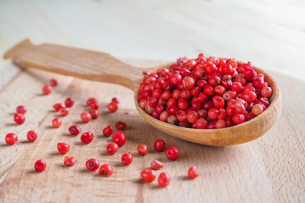 木のスプーンでピンクのコショウ豆。ソフトフォーカス。