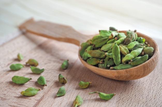Органические семена кардамона в деревянной ложке. индийская специя кардамон. мягкий фокус.