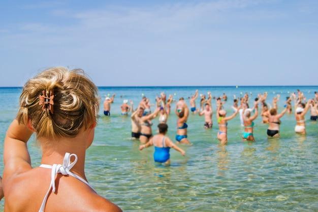 Аквааэробика. дама смотрит на водную анимацию с туристами в водах средиземного моря.