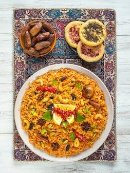 野菜ビリヤニ、白い木製のテーブルにベジタリアン料理。上面図。