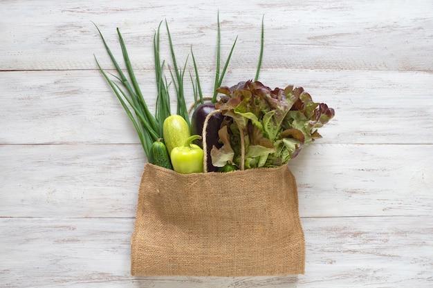 緑の野菜でいっぱいの再利用可能な黄麻布の袋、白い木製のテーブルのトップビュー