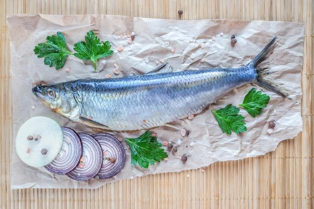 食欲をそそるニシンの切り身、玉ねぎ、レモン、羊皮紙のスパイス。