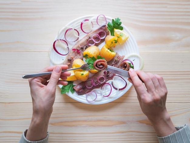 Простой деревенский обед с сельдью и икрой на тарелке.