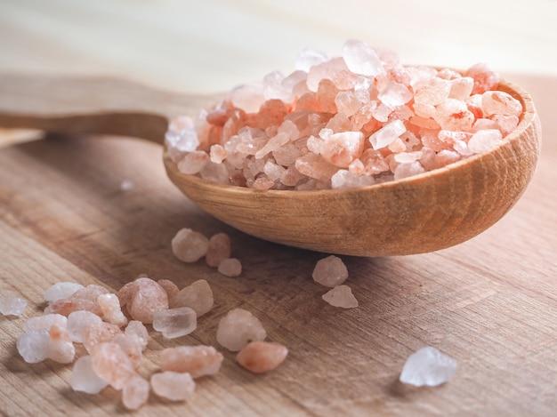 Большая розовая гималайская соль и деревянная ложка на деревянном столе.