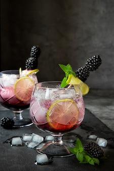 Сезонные безалкогольные напитки. жажда в жаркое летнее время. два стакана льда, воды, лайма и ягод шелковицы с мятой. кето диета, безалкогольные и алкогольные напитки. фруктовый коктейль